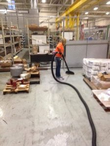 Restoration Technician Cleaning After Warehouse Flooding